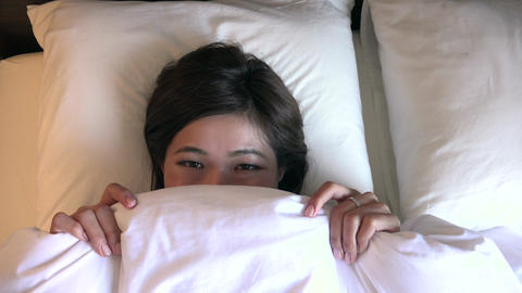 Face Of Shy Happy Young Woman Smiling Under Blankets Footage