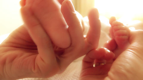 Mother tickling newborn baby's feet Footage