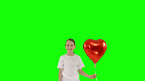 Little girl holding bundle of red heart shaped air balloons isolated on green Footage