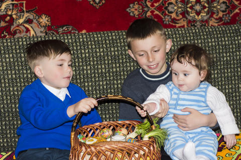 Two brothers and sisters are sitting in the room near the easter basket Fotografía