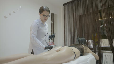 Beautiful young brunette with incredible body relaxing at spa clinic enjoying Footage