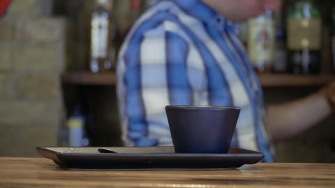 Empty cup on the bar counter, bartender makes coffee on blurred background Footage