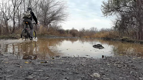 A cyclist rides through a puddle Footage