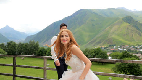 Wedding day. Happy newlyweds have fun against the backdrop of the mountains Image