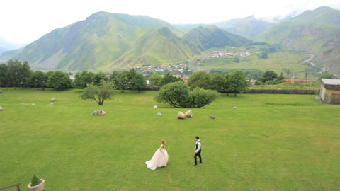 Happy newlyweds on a background of mountains on their wedding day 영상물