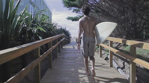 Surfer walking with surf board going towards the ocean Footage