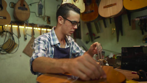 4 Man Lute Maker Artisan Tuning Guitar With A Diapason Footage