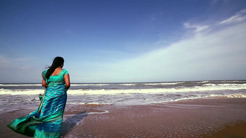 Beautiful girl standing and deep in thought on beach, Woman coming towards Live Action