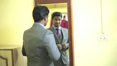 Groom is looking at the mirror,checking his appearance preparing for the wedding Footage