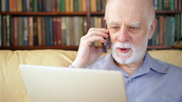 Senior man sitting at home with laptop and smartphone. Using cellphone Footage