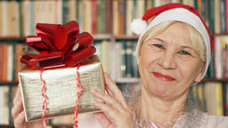 Senior woman with present. Pensioner in red hat with gift box with red ribbon Footage