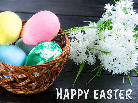 Basket with Easter eggs, white flowers on a dark wooden background フォト