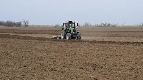 Lush and loosen the soil on the field before sowing. The tractor plows a field Live Action