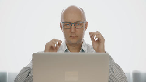 Serious man in glasses working on notebook computer and drinking tea from cup Footage