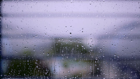 Raindrops on the window with blurred background Footage