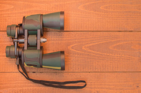 Binoculars protective khaki on wooden background, top view Fotografía