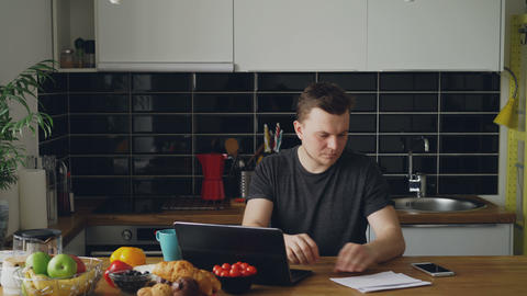 Handsome young man recieve good news reading paper letter in the kitchen while Footage
