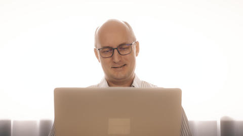 Smiling bald man in glasses working on notebook with good mood Live Action