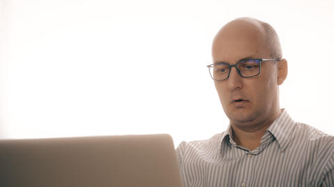 Sad man browsing email in notebook computer and looking into camera Live Action