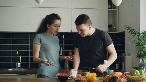 young curly woman showing something unpleasant in husband's phone while he is Footage
