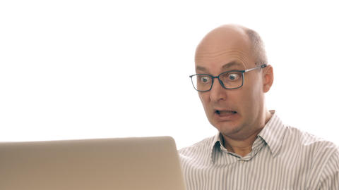 Portrait of a business man in glasses, with frightened look, sitting at laptop Footage