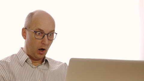 Portrait of a business man wearing glasses. Surprised man looks at laptop. The Live Action