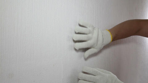 Man in glove showing how to remove old wallpaper Footage