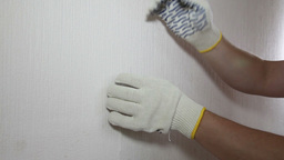 Man in glove showing how to remove old wallpaper Stock Video Footage