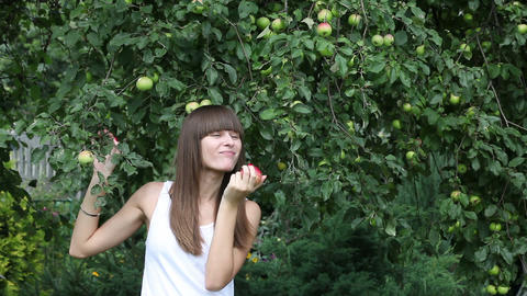 Pretty girl eating red apple in the garden Footage