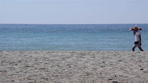 Man carrying a tray with sweets on the beach with fine sand by the seashore 6 Footage