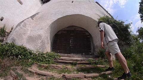 Man climbs the steps to the entrance under the old tower gate and looked through Footage