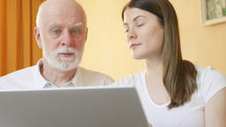 Senior father and daughter using laptop. Teen granddaughter teaching grandfather Footage