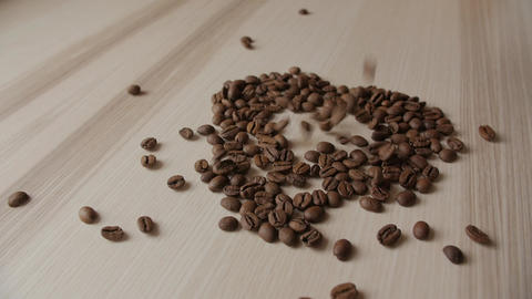 Coffee beans on a wooden table. Background of falling coffee beans. Heart of the Live Action