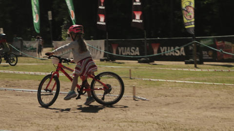 Little girl tries riding bicycle on zig zag training track Footage