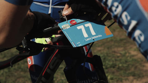 Athlete binds number on bicycle wheel at sportive race event Live Action