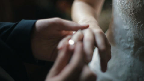 The groom puts the wedding ring on finger of the bride. marriage hands with Footage