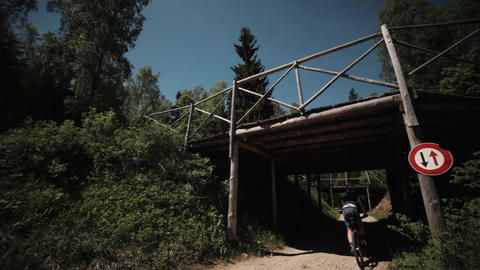 Bicycle freeride race in forest, athlete fast rides under wooden bridge Footage