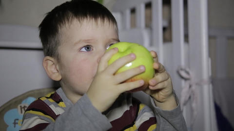 The child eats an apple sitting at a table in the room Footage