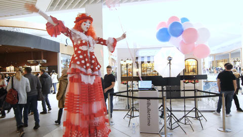 Actress in Clown Suit on Stilts Entertains People Footage