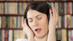 Happy female college student in university library listening music with big Footage