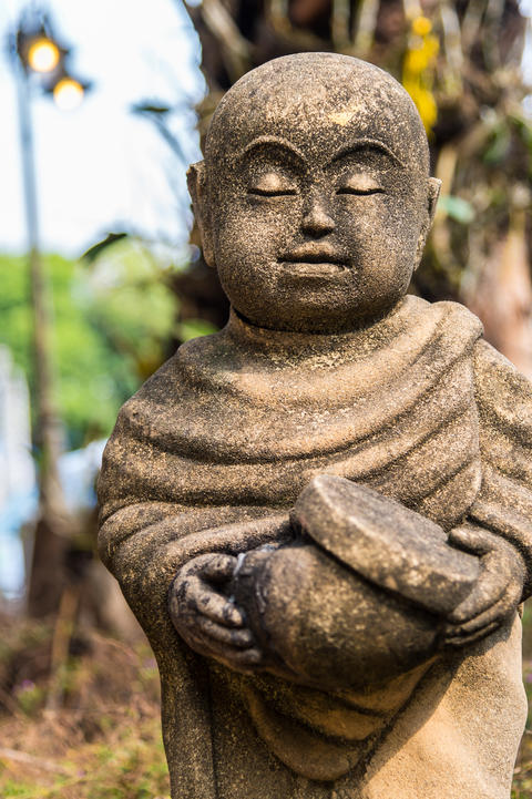 Old statue of a little monk standing and holding monk's alms-bowl フォト