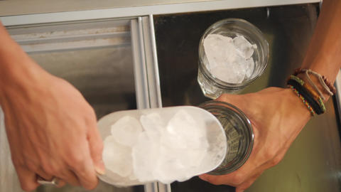 Barista Putting Scoop of Ice Cubes in Glass. Beginning of preparing light summer Footage
