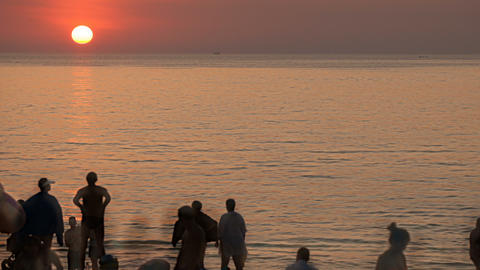 Silhouettes of people at sunset by the sea.Time lapse Footage