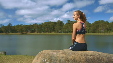 Girl with Ponytail Sits on Boulder Watches River Bank Footage