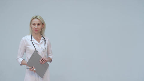 Serious Young female doctor in white room writing Footage