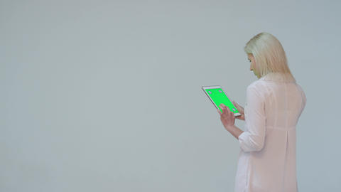 Doctor pressing the green screen of a tablet computer against a white background Footage