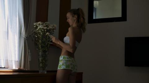 Blond Girl Adjusts Flowers in Vase and Leaves Room Footage