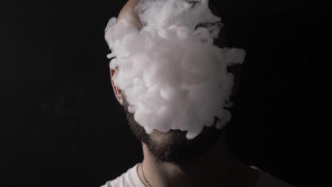 Bold young male musician vaper with beard vapes and blows on his mouth a huge Live Action