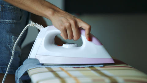 Woman Irons with White and Pink Flatiron on Desk Footage