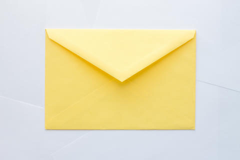 Yellow envelope on white background Fotografía